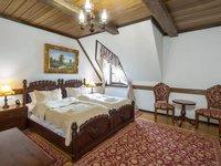 Stylové, době zařízené pokoje s masivním nábytkem.