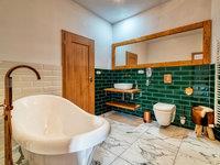 Koupelna s lahvově zelenou koupelnou - pivní hotel Zlatá kráva
